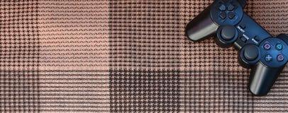 Nowożytny czarny wideo gry kontroler kłama na w kratkę czerni szkocka krata, beżu lub przesłona i Plastikowy joystick jako pojęci zdjęcie royalty free