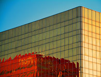 Nowożytny czerwony budynek odbijający w złotym budynku fotografia stock