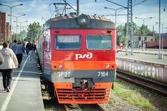 Nowożytny czerwony podmiejski elektryczny pociąg stoi przy stacją Fotografia Royalty Free