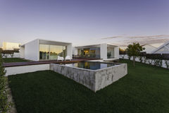 Nowożytny dom z ogrodowym pływackim basenem i drewnianym pokładem Obrazy Royalty Free