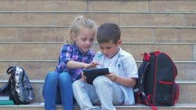 Nowożytny dzieciństwo, ucznie z plecakami używa cyfrowego pastylki obsiadanie na krokach szkoła w na wolnym powietrzu podczas rec