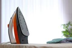 Nowożytny elektryczny żelazo i odziewa na pokładzie indoors fotografia royalty free