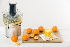 Nowożytny elektryczny juicer i świeżo przygotowany sok pomarańczowy zdjęcie stock