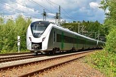 Nowożytny elektryczny regionalność pociąg biega na pasa ruchu śladzie przez naturalnych otoczeń Zdjęcia Stock