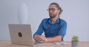 Nowożytny freelancer pisać na maszynie na laptopie w lekkich biurowych uśmiechach joyfully w kamerę z ponytail i eyeglasses zbiory wideo