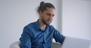 Nowożytny freelancer z ponytail pracuje z laptopu obsiadaniem w karle w lekkich biuro zwrotach kamera i śmiać się zbiory