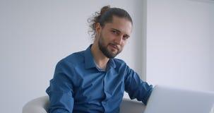 Nowożytny freelancer z ponytail pracuje z laptopu obsiadaniem w karle w lekkich biuro zwrotach kamera i uśmiechy zbiory wideo