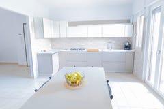 Nowożytny, jaskrawy, czysty, kuchenny wnętrze z stali nierdzewnych urządzeniami, i friut jabłko na stole w luksusu domu Obraz Royalty Free