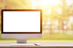 Nowożytny komputer stacjonarny na drewnianym stołu i abstrakta świetle zamazuje obraz stock