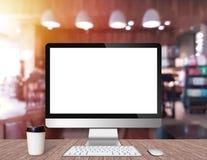 Nowożytny Komputerowy monitor na drewnianym biurku z sklep z kawą obraz royalty free