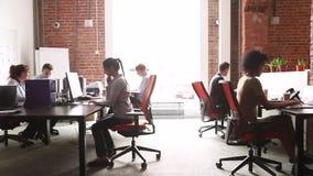 Nowożytny korporacyjny biuro z wielokulturowymi pięcioliniowych pracowników grupowymi używa komputerami zbiory