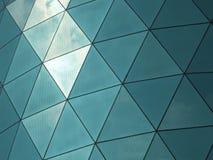 Nowożytny korporacyjny budynek z graniastą wzorzystością odzwierciedlał okno tafle odbija chmury i niebo zdjęcie stock