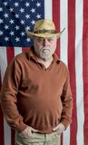 Nowożytny kowboj pozuje będący ubranym kapelusz przed flaga amerykańską obraz royalty free