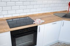 Nowo?ytny kuchenny meble z wsp??czesnym kitchenware jak kapiszon, czarna indukcji kuchenka i piekarnik, zdjęcia royalty free