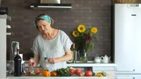 Nowożytny kuchenny wnętrze, gospodyni domowa portret Szczęście blondynki starsza kobieta w kuchennych trzyma szkłach, czerwone wi zdjęcie wideo