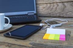 Nowożytny laptop, pastylka, telefon komórkowy i kleiste notatki na stole, fotografia royalty free