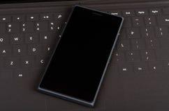Nowożytny mądrze telefon komórkowy na płaskiej klawiaturze Obraz Stock