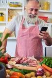 Nowożytny mężczyzna używa telefon znajdować przepis w internecie Obraz Royalty Free