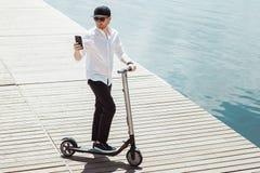 Nowożytny mężczyzna ubierał białych koszula i czerni spodnia używać jego przy drewnianym molem z elektryczną hulajnogą telefon po zdjęcie royalty free