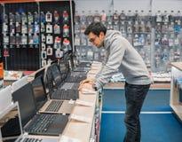 Nowożytny męski klient wybiera laptop w komputerowym sklepie zdjęcie stock