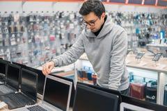 Nowożytny męski klient wybiera laptop w komputerowym sklepie fotografia royalty free