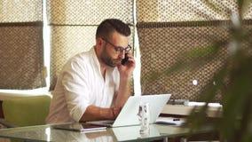 Nowożytny młody męski biznesmen opowiada na telefonie w białej brodzie i koszula, pracujący na laptopie, robi notatkom w a zbiory