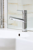 Nowożytny metalu faucet na białym ceramicznym obmycie stojaku fotografia stock