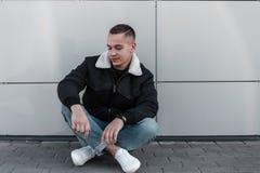 Nowożytny miastowy młody człowiek z modną fryzurą w rocznika czerni kurtce w niebieskich dżinsach w białych sneakers cieszy się w obraz stock
