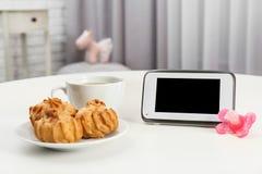 Nowożytny monitor, filiżanka kawy, ciastka i pacyfikator na stole indoors, przestrzeń dla teksta fotografia stock
