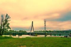 Nowożytny most w Warszawa przez rzekę obok stadionu futbolowego w wieczór z położenia słońcem Obraz Royalty Free