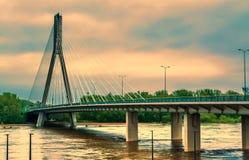 Nowożytny most w Warszawa przez rzekę obok stadionu futbolowego w wieczór z położenia słońcem Zdjęcia Royalty Free