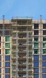 nowożytny multistory budynek mieszkaniowy w budowie z rusztowania i dźwignika ramami pod niebieskim niebem obraz stock