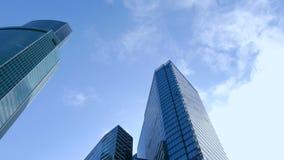 Nowożytny odzwierciedlający budynek i szybkie poruszające biel chmury na niebieskim niebie zbiory