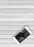 Nowożytny telefon komórkowy z łamanym ekranem na biały drewnianym fotografia stock