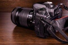 Nowożytna dslr kamera na ciemnym drewnianym stole zdjęcia stock