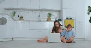 Nowo?ytna mieszkanie mama i dwa syna siedzi na pod?odze w ?ywym izbowym spojrzeniu przy laptopu ekranem zdjęcie wideo