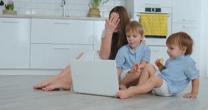 Nowo?ytna mieszkanie mama i dwa syna siedzi na pod?odze w ?ywym izbowym spojrzeniu przy laptopu ekranem zbiory