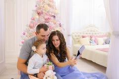 Nowożytna rodzina opowiada z krewnymi na Skype w przestronnej sypialni Zdjęcia Stock