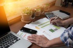 Nowożytni ludzie robi biznesowi, wykresom i mapom demonstruje na drewnianym biurku w biurze, Fotografia Royalty Free