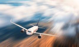 Nowożytny samolot z ruch plamy skutkiem lata nad niskimi chmurami Fotografia Stock