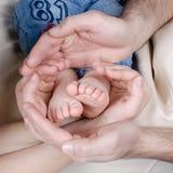 Nowonarodzeni dziecko cieków rodzice trzyma w rękach Mamy i tata chwyta dziecka nogi Fotografia Royalty Free