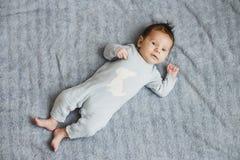 Nowonarodzona ładna chłopiec w błękitnym sleepwear lying on the beach na popielatym prześcieradle, odgórny widok zdjęcia stock