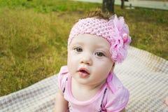 Nowonarodzona dziewczyna w pięknym parku outdoors, kłamający na koc i patrzejący kamerę Obraz Royalty Free