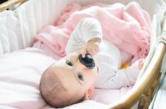 Nowonarodzona różowa kołysankowa chwyta czerni pacyfikatoru ręka Fotografia Royalty Free
