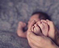 Nowonarodzone dziecko nogi w rodzic rękach Obrazy Stock
