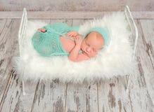 Nowonarodzony dosypianie na łóżku polowym z białą miękką koc fotografia royalty free