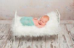 Nowonarodzony dosypianie na łóżku polowym z białą miękką koc zdjęcie stock