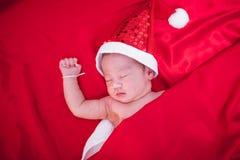 Nowonarodzony dziecka dosypianie na Santa het i czerwonym tle zdjęcia royalty free