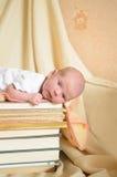 Nowonarodzony dziecka lying on the beach na stosie książki obraz stock