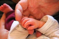Nowonarodzony dziecka mienia adult& x27; s palec zdjęcia stock